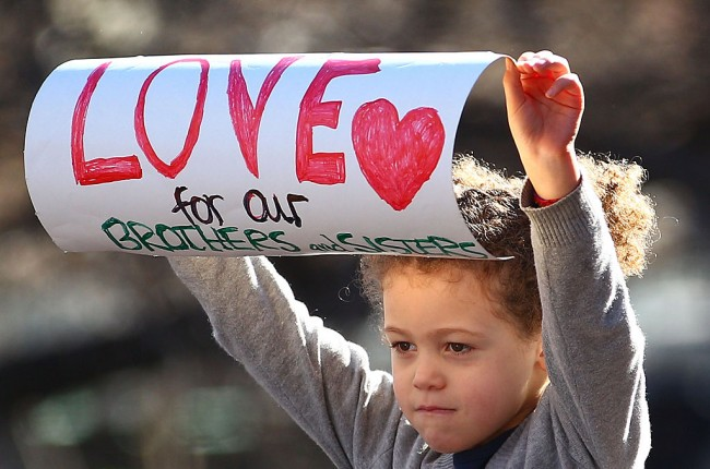 A young child holds a sign aloft to support the Black Lives Matter movement.