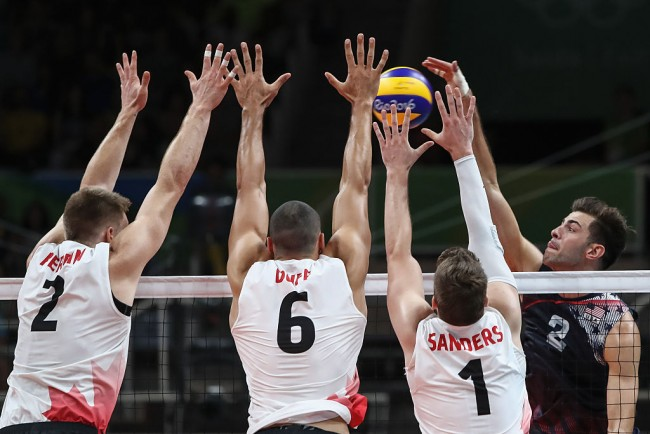 Aaron Russell of the United States (R) jumps to spike the ball against Jonh Gordon Perrin #2,