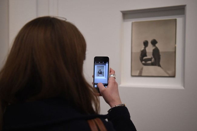 A journalist uses their phone to take a picture at the press preview for 'Vogue 100: A Century of Style'