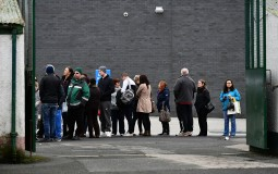 People queue outside waiting to get in the building.