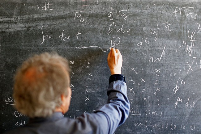 Professor writes mathematical equations on the board.