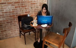 A woman uses attends an online class at a local restaurant.