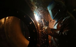 A welder works on a tank. Artificial Intelligence may replace manual labor and high decision making job roles