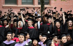 Harvard University Law School students stand and wave gavels in celebration at commencement ceremonies
