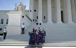 International University graduates throw their velvet caps into the air while posing for photographs