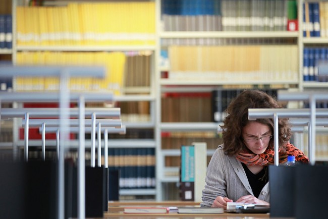 A student is reading entrepreneurial materials in the university library.