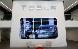 The Tesla logo is displayed inside of the new Tesla flagship facility in San Francisco, California