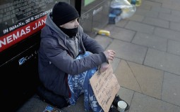 A homeless man begs for small change on the streets of Manchester