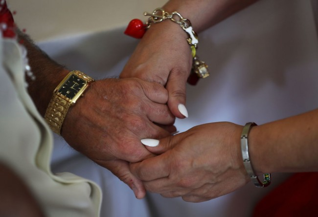 A couple holds hands as they participate in a group Valentine's day wedding ceremony at the National Croquet Center on February 14, 2017 in West Palm Beach, Florida.